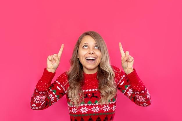 Młoda kobieta w czerwonym świątecznym swetrze z jeleniem wskazuje na puste miejsce na tekst powitalny