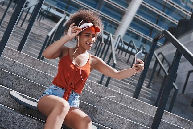 Młoda kobieta w daszku i słuchawkach w swobodnym stylu na ulicy sitt