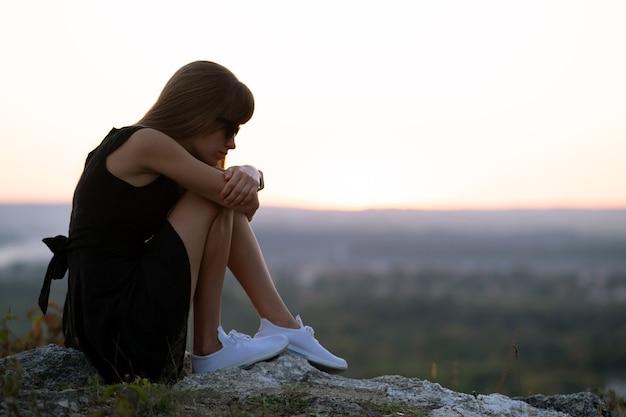 Młoda kobieta w depresji w czarnej krótkiej letniej sukience siedzi na skale, myśląc na zewnątrz o zachodzie słońca. modna kobieta kontemplując w ciepły wieczór na łonie natury.