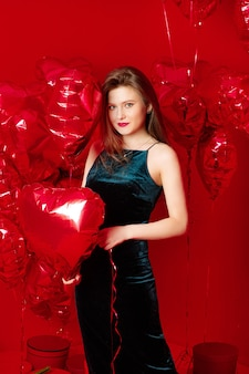 Młoda kobieta w długiej sukni z czerwonymi balonami w kształcie serca
