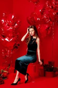 Młoda Kobieta W Długiej Sukni Z Czerwonymi Balonami W Kształcie Serca Premium Zdjęcia