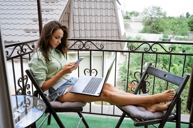Młoda kobieta w domowych ubraniach siedzi na balkonie, przy stole pracuje z telefonem przy laptopie w letnie popołudnie