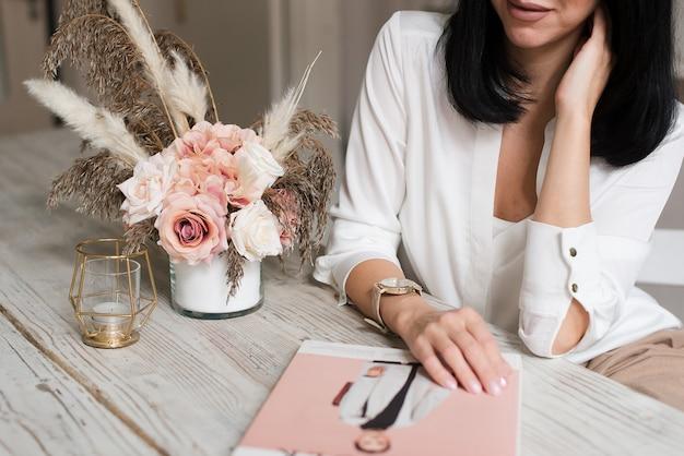 Młoda kobieta w domowym biurze. dziewczyna pracuje nad nowym projektem startowym. kobiece myślenie i pisanie w terminarzu lub dzienniku w miejscu pracy w minimalistycznym stylu.