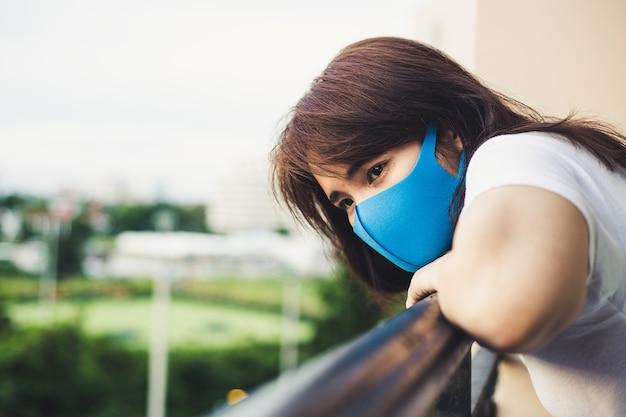 Młoda kobieta w domu izolacji stojącej na balkonie