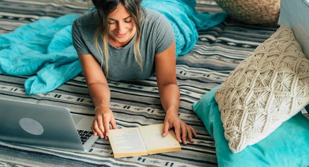 Młoda kobieta w domu r. na podłodze studiując z komputera przenośnego i książki