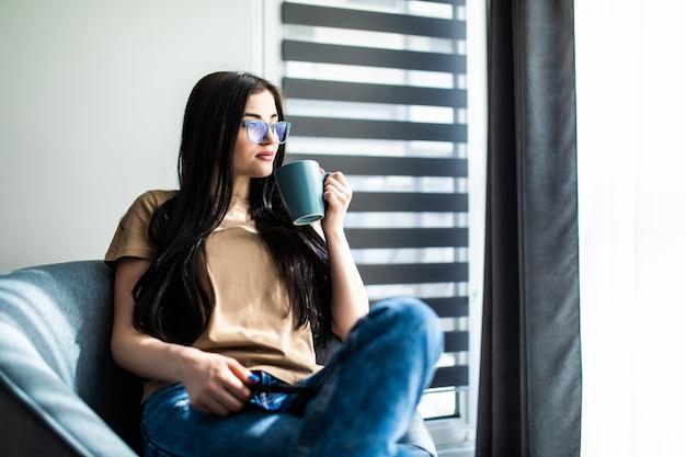 Młoda kobieta w domu siedzi na nowoczesnym krześle przed oknem, relaksując się w swoim salonie, pijąc kawę