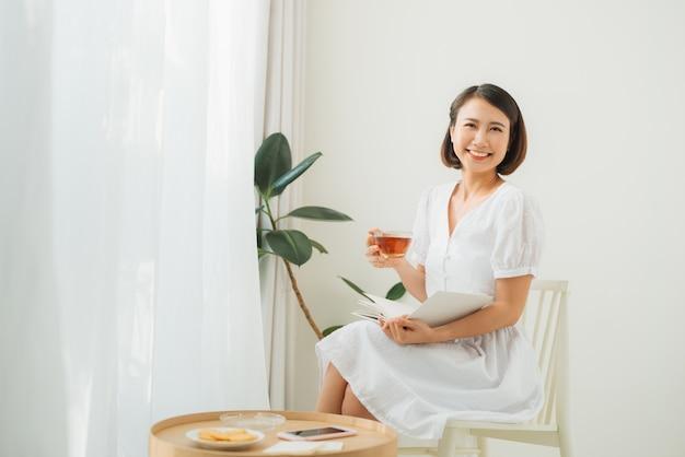 Młoda kobieta w domu siedzi przy oknie, relaksując się w swoim salonie, czytając książkę i pijąc herbatę