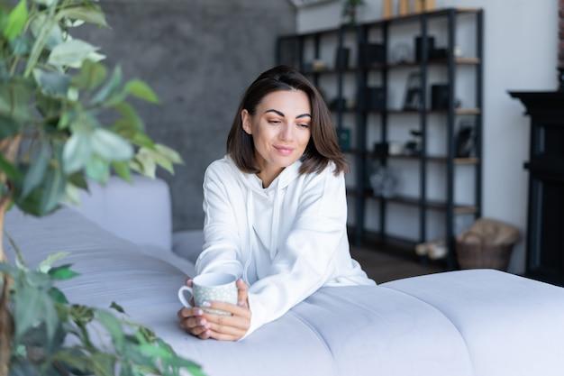Młoda kobieta w domu w białej bluzie z kapturem na kanapie siedzi spokojnie, cieszy się samotnością