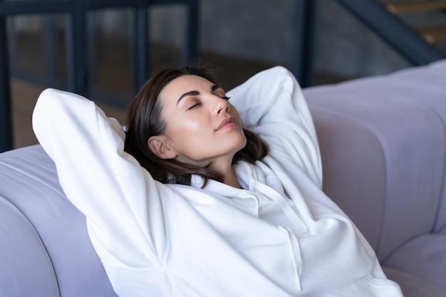 Młoda kobieta w domu w białej bluzie z kapturem na kanapie spokojnie siedzi z zamkniętymi oczami