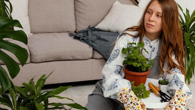 Młoda kobieta w domu z garnkiem roślin i narzędzi ogrodniczych