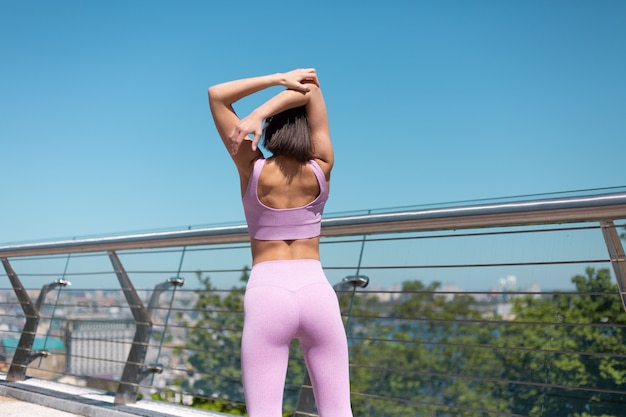 Młoda kobieta w dopasowanej odzieży sportowej na moście w gorący słoneczny poranek rozciągnąć się