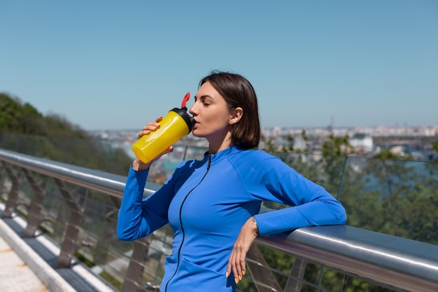 Młoda kobieta w dopasowanej odzieży sportowej na moście w gorący słoneczny poranek z butelką wody shaker spragniony po treningu zmęczony piciem