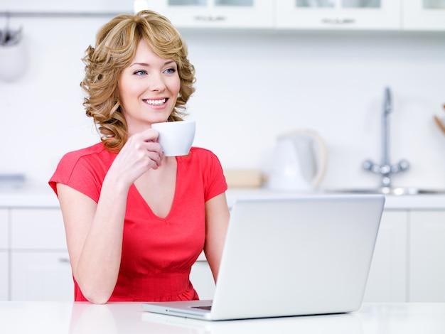 Młoda kobieta w dorywczo z filiżanką kawy i laptopem w kuchni