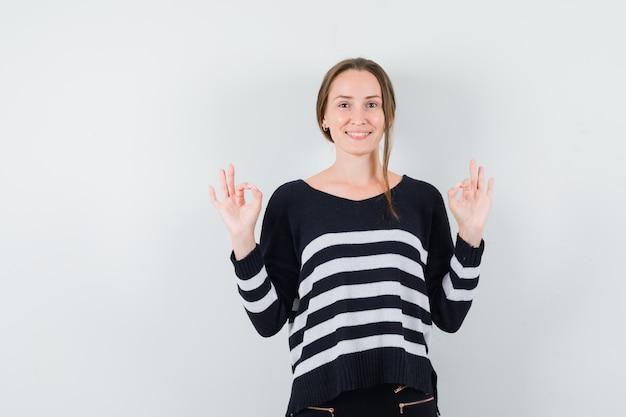 Młoda kobieta w dzianinie w paski i czarnych spodniach pokazuje znak ok obiema rękami i wygląda na szczęśliwą