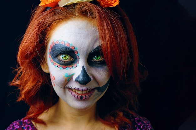 Młoda kobieta w dzień martwej maski czaszki