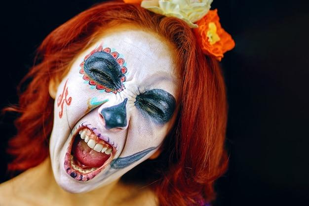 Młoda kobieta w dzień zmarłych maski czaszka sztuka twarz kobieta z makijażem czaszki i czerwonymi włosami krzyczącą ...