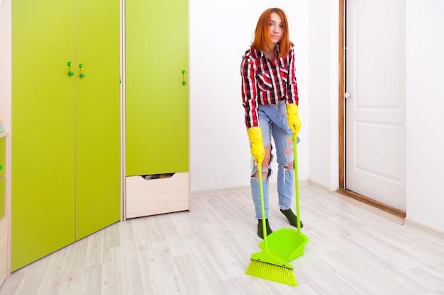 Młoda kobieta w dżinsach i koszuli w kratę zamiata podłogę zieloną miotłą i łopatą