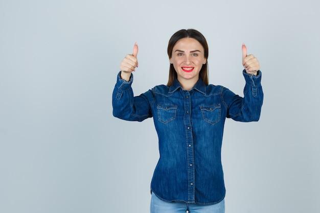 Młoda kobieta w dżinsowej koszuli i dżinsach pokazując kciuki do góry i patrząc efektownie