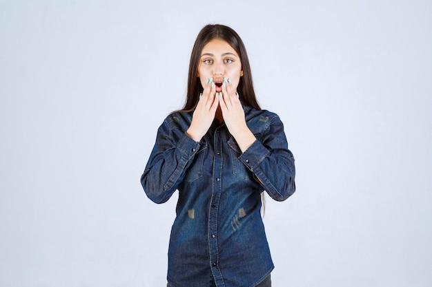 Młoda kobieta w dżinsowej koszuli jest zaskoczona i podekscytowana