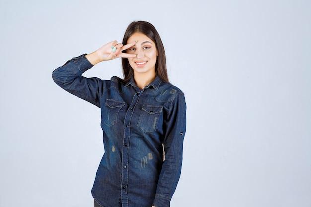 Młoda kobieta w dżinsowej koszuli patrząc przez palce