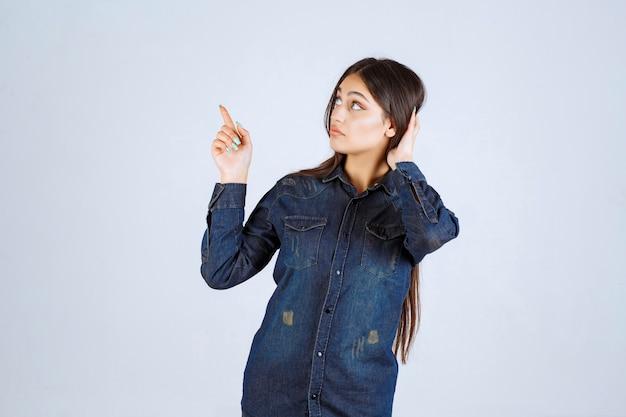 Młoda kobieta w dżinsowej koszuli, podnosząc ręce i wskazując na coś powyżej
