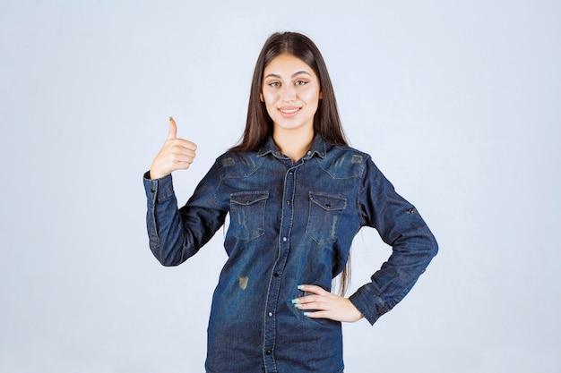 Młoda kobieta w dżinsowej koszuli pokazano znak radości