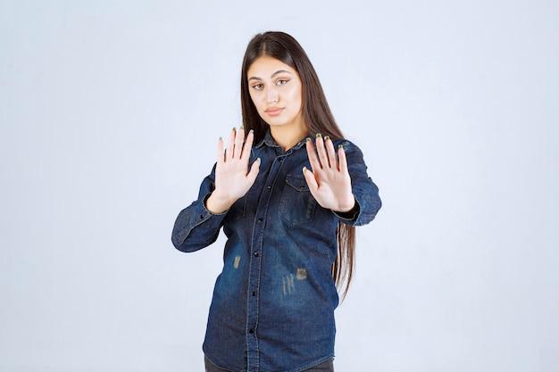 Młoda kobieta w dżinsowej koszuli próbuje coś powstrzymać i powstrzymać