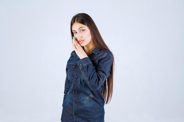 Młoda kobieta w dżinsowej koszuli szepcze i plotkuje