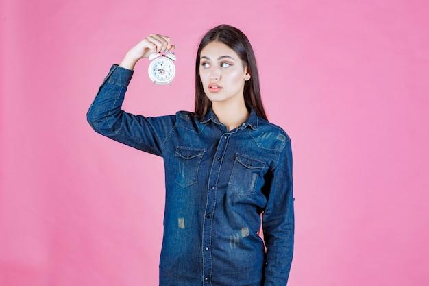 Młoda kobieta w dżinsowej koszuli trzyma i promuje budzik