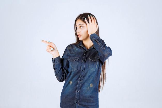 Młoda kobieta w dżinsowej koszuli, wskazując lewą stronę z emocjami twarzy