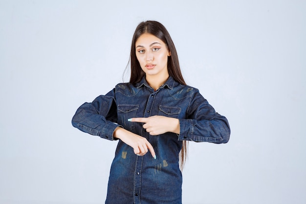 Młoda kobieta w dżinsowej koszuli, wskazując na jej czas