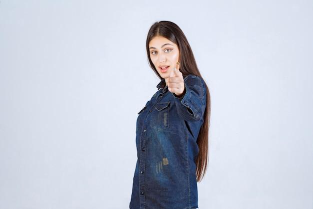 Młoda kobieta w dżinsowej koszuli, wskazując na osobę przed nią