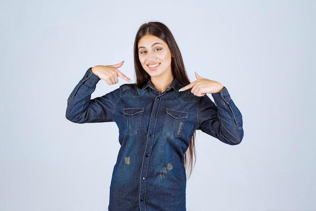 Młoda kobieta w dżinsowej koszuli, wskazując na siebie