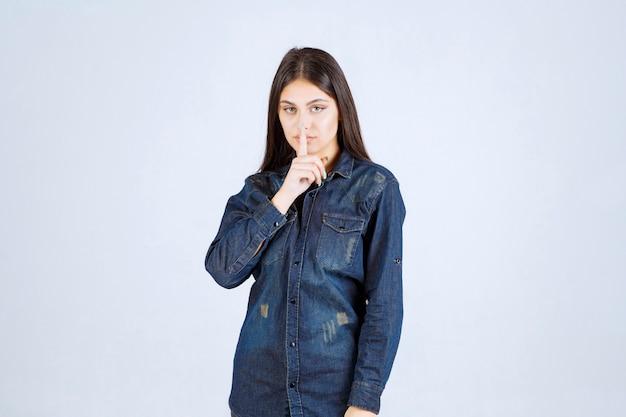 Młoda kobieta w dżinsowej koszuli, wskazując na usta i prosząc o ciszę