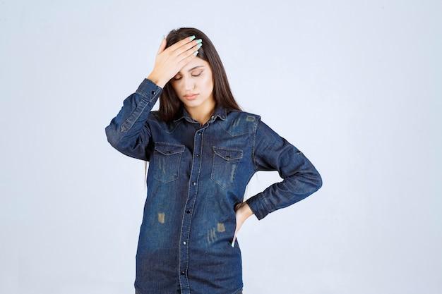 Młoda kobieta w dżinsowej koszuli wygląda na wyczerpaną i śpiącą