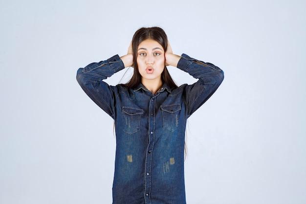 Młoda kobieta w dżinsowej koszuli wygląda na zaskoczoną i podekscytowaną
