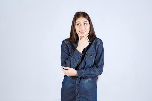 Młoda kobieta w dżinsowej koszuli wygląda na zdezorientowaną i zamyśloną