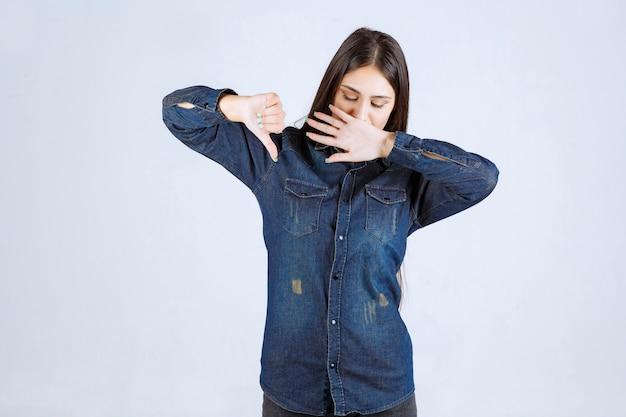 Młoda kobieta w dżinsowej koszuli wygląda śpiąco i pokazuje kciuk w dół
