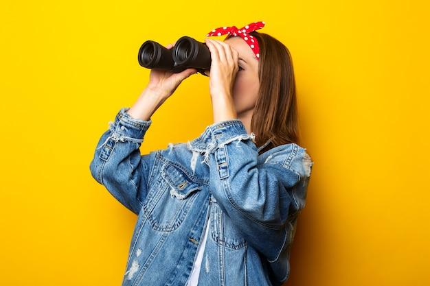 Młoda kobieta w dżinsowej kurtce i tratwie na głowie patrzy przez lornetkę na żółtej ścianie. transparent.