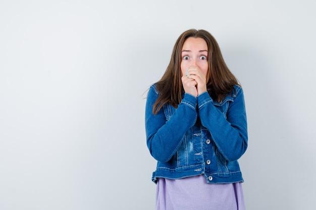Młoda kobieta w dżinsowej kurtce trzymając ręce na ustach i patrząc przestraszony, widok z przodu.