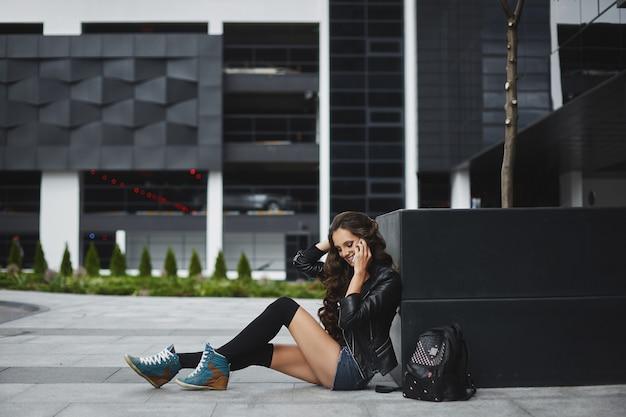 Młoda kobieta w dżinsowych szortach i skórzanej kurtce rozmawia przez telefon i siedzi na ulicy europejskiego miasta w letni dzień