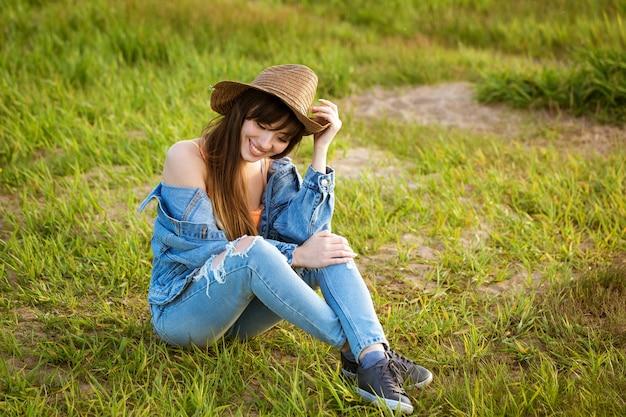 Młoda kobieta w dżinsowym garniturze i kapeluszu siedzi na trawie
