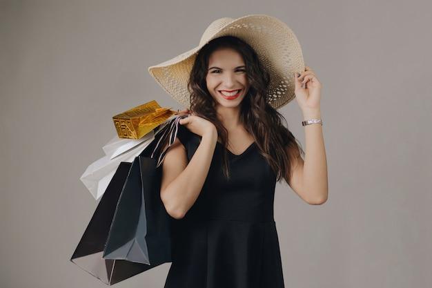 Młoda kobieta w eleganckiej czarnej sukni i letnim kapeluszu