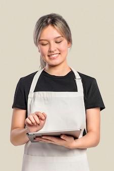 Młoda kobieta w fartuchu przy użyciu tabletu