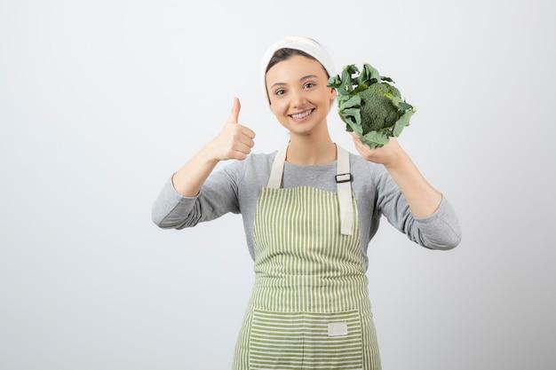 Młoda kobieta w fartuchu trzymająca świeże brokuły i pokazująca kciuk w górę