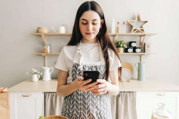 Młoda kobieta w fartuchu używać smartfona w kuchni
