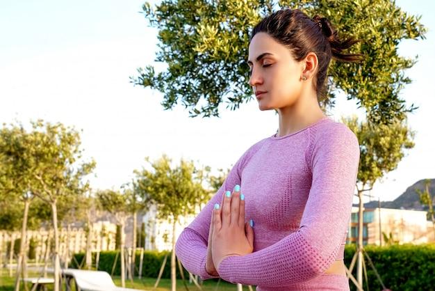 Młoda kobieta w fioletowej koszuli i spodniach na trawie w ciągu dnia w zielonym parku medytacji i ćwiczeń jogi w różnych pozach
