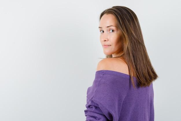 Młoda kobieta w fioletowej koszuli patrząc na kamery i wyglądająca rozsądnie.