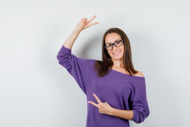 Młoda kobieta w fioletowej koszuli pokazano znak zwycięstwa i szczęśliwy, widok z przodu.