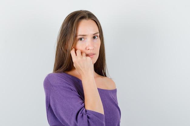 Młoda kobieta w fioletowej koszuli, trzymając palce na policzku i patrząc rozsądnie, widok z przodu.